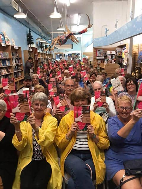 Readers at a book tour event for Wade Rouse/Viola Shipman holding up copies of THE RECIPE BOX